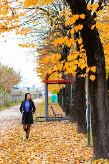 Portret van een jonge vrouw die in de herfstpark loopt