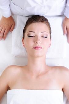 Portret van een jonge vrouw die in de schoonheidssalon ligt vóór kuuroordprocedures