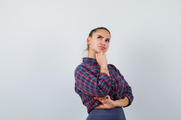 Portret van een jonge vrouw die in een denkende pose staat in een geruit hemd, een broek en een peinzend vooraanzicht kijkt