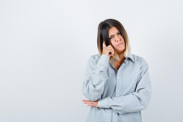 Portret van een jonge vrouw die in een denkende pose staat in een te groot shirt en er peinzend vooraanzicht uitziet