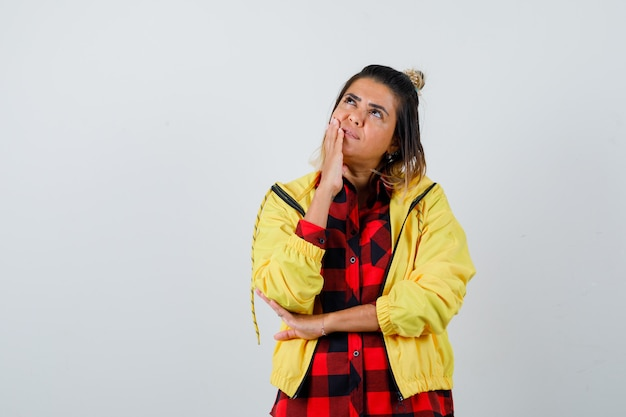 Portret van een jonge vrouw die in een denkende pose staat terwijl ze opkijkt in een geruit hemd, een jas en een verbaasd vooraanzicht kijkt