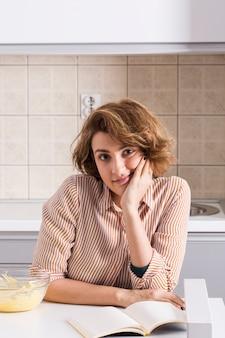 Portret van een jonge vrouw die in keuken aan camera kijkt