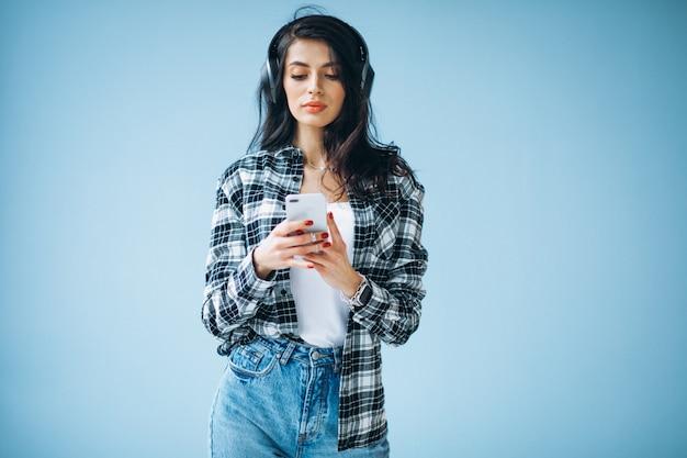 Portret van een jonge vrouw die in oortelefoons aan muziek luistert