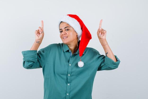 Portret van een jonge vrouw die in shirt, kerstmuts omhoog wijst en zelfverzekerd vooraanzicht kijkt