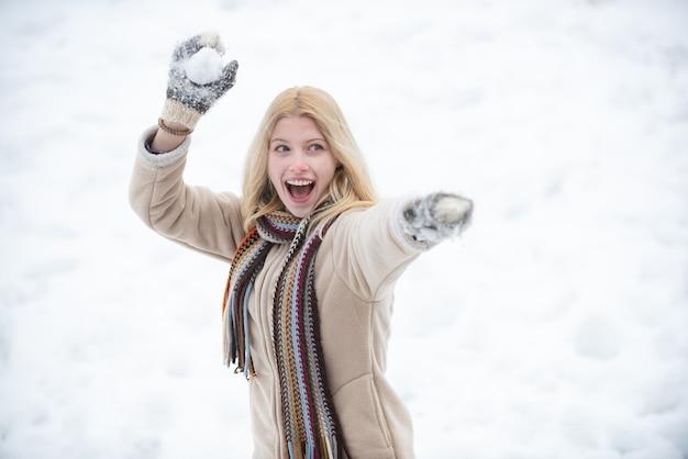 Portret van een jonge vrouw die in sneeuw probeert te verwarmen. modellen met plezier in winterpark. gelukkig