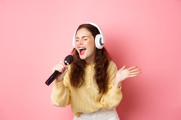 Portret van een jonge vrouw die karaoke zingt, hoofdtelefoons draagt en lied uitvoert, microfoon houdt, die zich tegen roze muur bevindt.