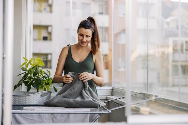 Portret van een jonge vrouw die klusjes doet, de was op het balkon stapelt en uitspreidt. een glimlachende vrouw gekleed in vrijetijdskleding legt handdoeken op het terras op een zonnige zomerdag