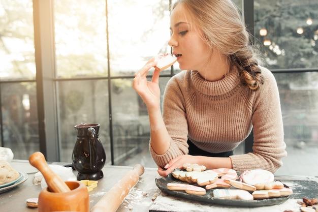 Portret van een jonge vrouw die koekjeshart eet