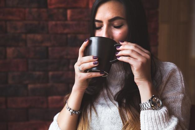 Portret van een jonge vrouw die koffie drinkt
