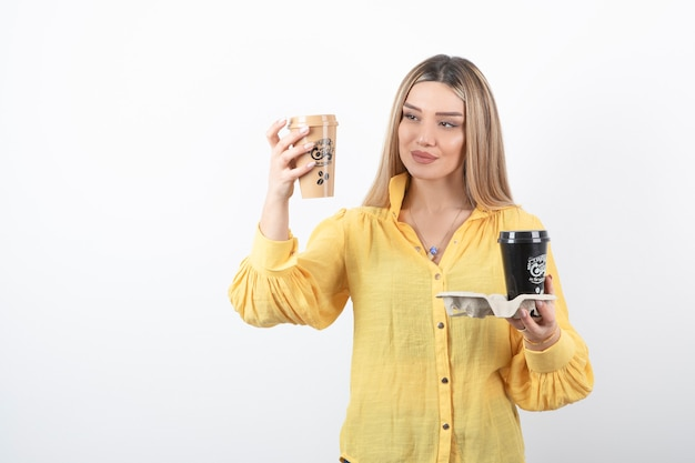 Portret van een jonge vrouw die kopjes koffie op de witte muur bekijkt.
