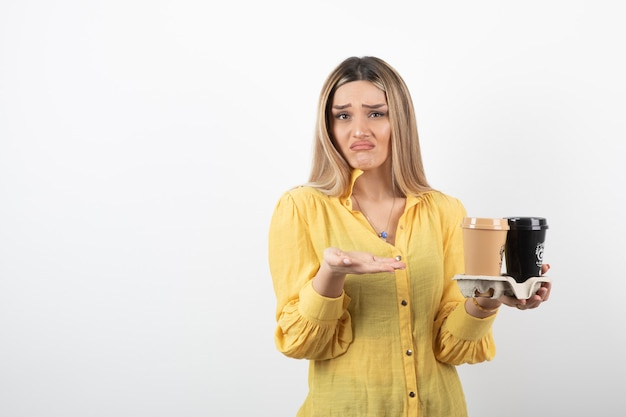 Portret van een jonge vrouw die kopjes koffie vasthoudt en niet weet wat ze moet doen.