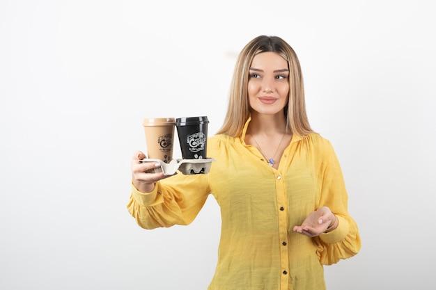 Portret van een jonge vrouw die kopjes koffie vasthoudt en op een witte muur staat.