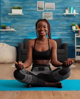 Portret van een jonge vrouw die lacht en thuis yoga beoefent, zittend in lotushouding op mat mediteren, mindfulness beoefenen
