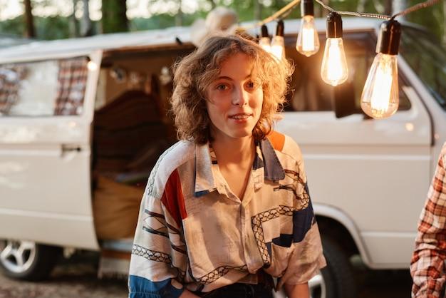 Portret van een jonge vrouw die lacht naar de camera terwijl ze 's avonds buiten op een picknick zit