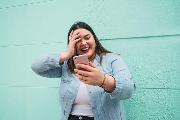 Portret van een jonge vrouw die lacht tijdens het typen van tekstbericht op haar mobiele telefoon buitenshuis