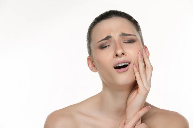Portret van een jonge vrouw die lijdt aan vreselijke tandpijn