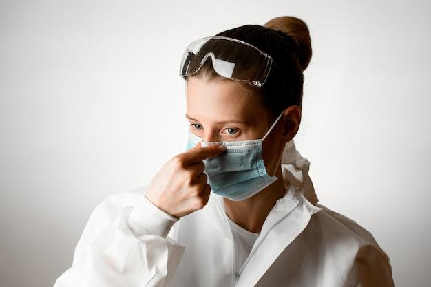 Portret van een jonge vrouw die medisch masker op haar gezicht corrigeert