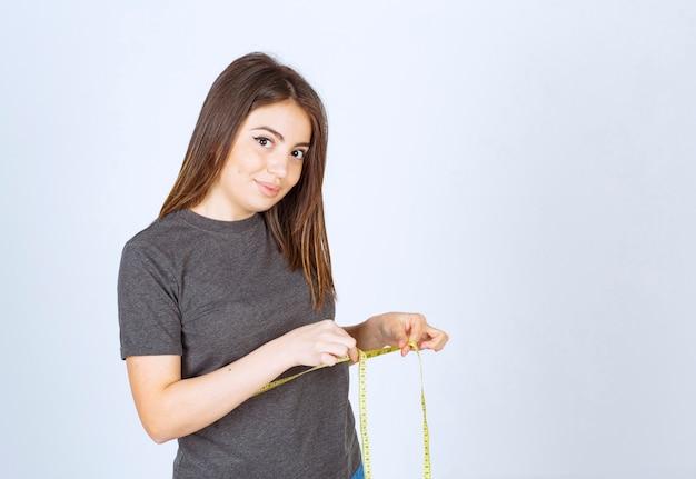 Portret van een jonge vrouw die meetlint om haar middel houdt en naar de camera kijkt.