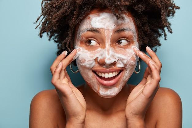 Portret van een jonge vrouw die met afro-kapsel haar huid wast