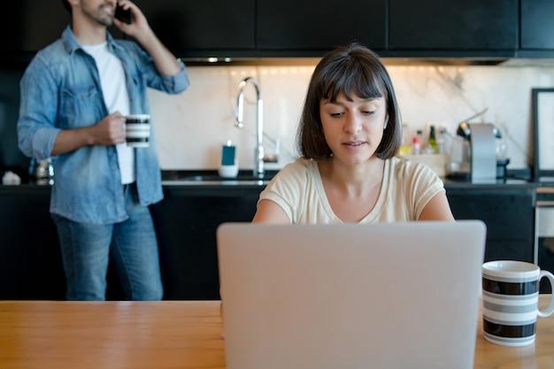 Portret van een jonge vrouw die met een laptop werkt vanuit huis terwijl de mens aan de telefoon spreekt