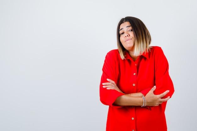Portret van een jonge vrouw die met gekruiste armen in een rood oversized shirt staat en zelfverzekerd vooraanzicht kijkt