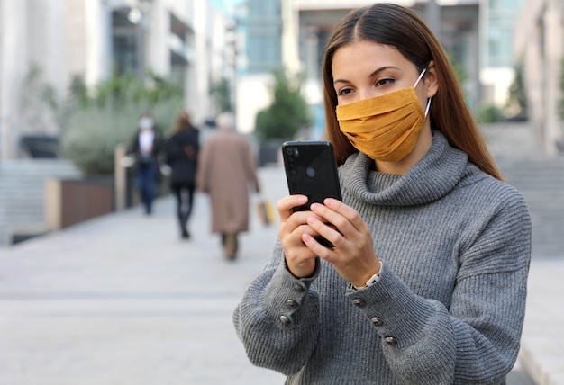 Portret van een jonge vrouw die met gezichtsmasker buiten zitten aangezien lockdown bedrijfsmartphone opent