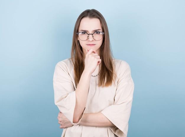 Portret van een jonge vrouw die met haar vinger aan haar hoofd denkt en naar de camera kijkt