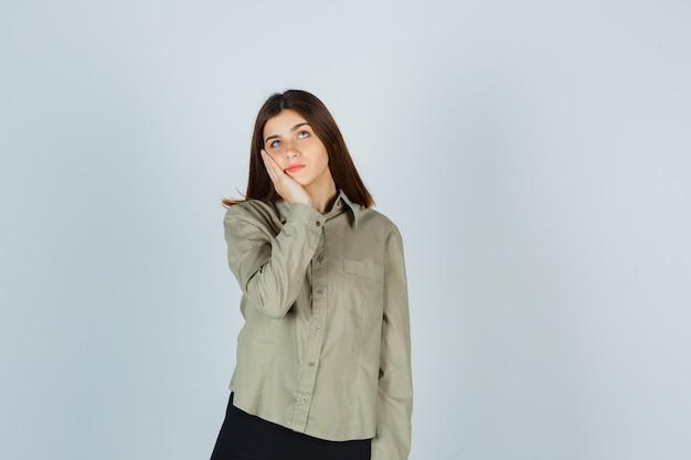 Portret van een jonge vrouw die met haar wang op de handpalm leunt, omhoog kijkt in shirt, rok en hoopvol vooraanzicht