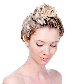 Portret van een jonge vrouw die met het inzepen hoofd neerkijkt - geïsoleerd op wit