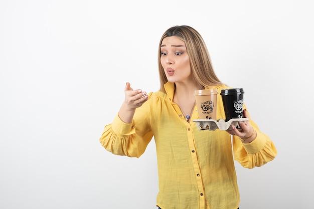 Portret van een jonge vrouw die met kopjes koffie haar hand op witte achtergrond bekijkt.