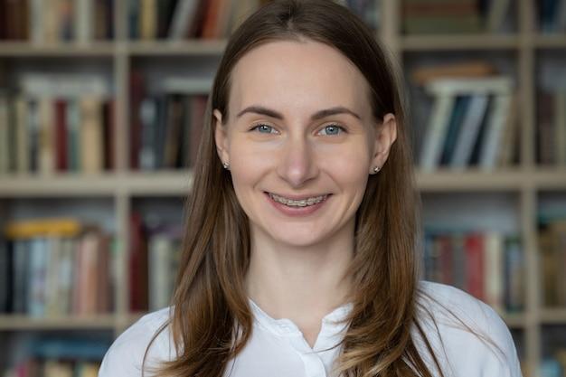 Portret van een jonge vrouw die met steunen op haar tanden tegen een bibliotheekboekenrek glimlacht