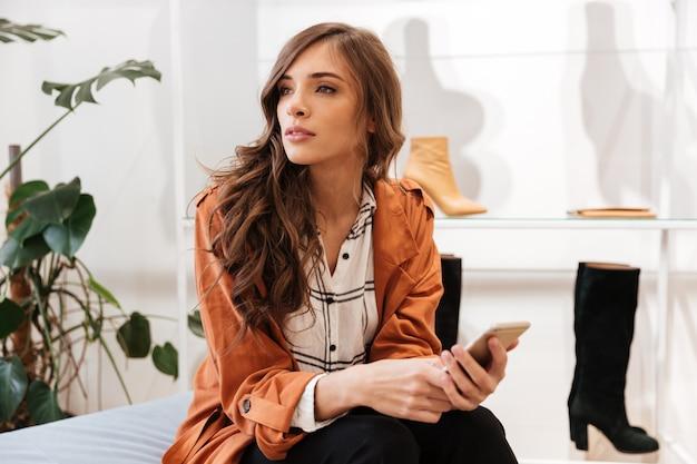 Portret van een jonge vrouw die mobiele telefoon houdt