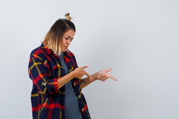 Portret van een jonge vrouw die naar beneden wijst in een geruit overhemd en er zelfverzekerd uitziet