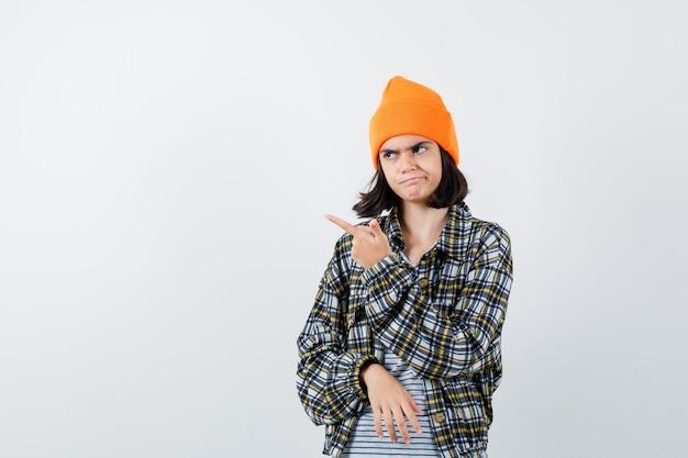 Portret van een jonge vrouw die naar boven wijst in een geruit overhemd met oranje hoed en er somber uitziet