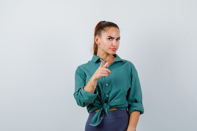 Portret van een jonge vrouw die naar de camera in een groen shirt wijst en er serieus vooraanzicht uitziet