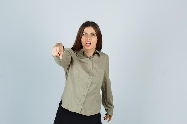 Portret van een jonge vrouw die naar de camera in shirt, rok wijst en er agressief vooraanzicht uitziet