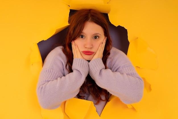 Portret van een jonge vrouw die naar de camera kijkt door een gescheurd gat in een papieren muur.