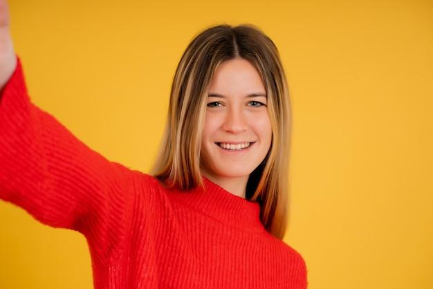 Portret van een jonge vrouw die naar de camera kijkt en glimlacht terwijl ze een selfie in de studio maakt.
