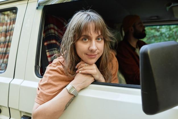 Portret van een jonge vrouw die naar de camera kijkt terwijl ze samen met haar vrienden met de bus reist