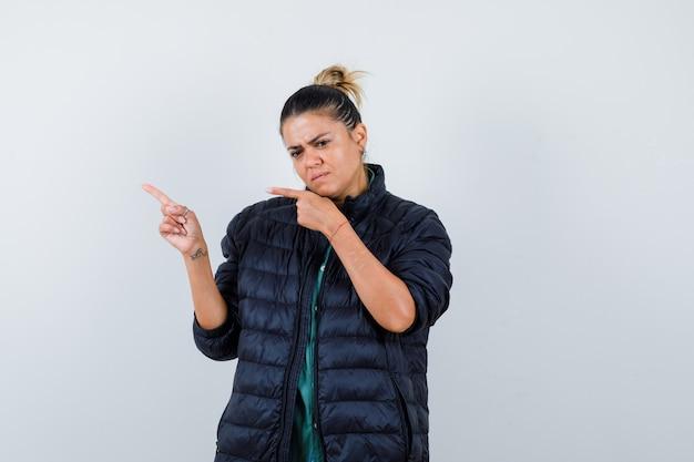 Portret van een jonge vrouw die naar de linkerbovenhoek in een pufferjack wijst en besluiteloos vooraanzicht kijkt