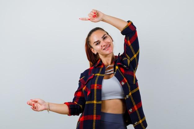 Portret van een jonge vrouw die naar de linkerkant wijst in crop-top, geruit hemd, broek en er vrolijk vooraanzicht uitziet