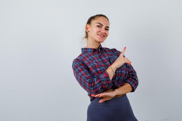 Portret van een jonge vrouw die naar de rechterbovenhoek wijst in een geruit hemd, een broek en een gelukkig vooraanzicht kijkt