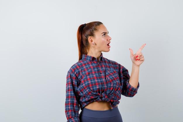 Portret van een jonge vrouw die naar de rechterbovenhoek wijst in een geruit hemd, een broek en een verbaasd vooraanzicht kijkt