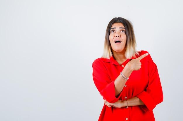 Portret van een jonge vrouw die naar de rechterbovenhoek wijst in een rood oversized shirt en een verbaasd vooraanzicht kijkt