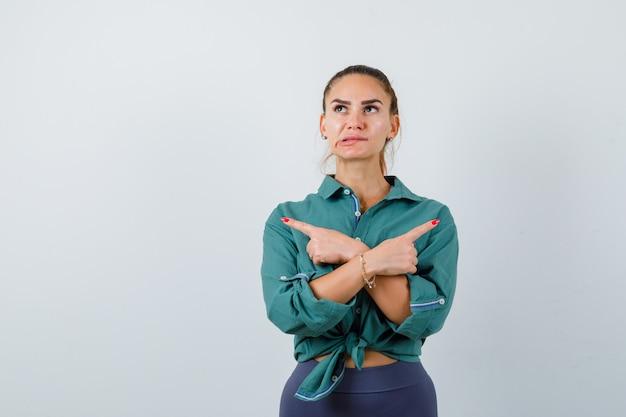 Portret van een jonge vrouw die naar de tegenovergestelde richting wijst, lip bijt in een groen shirt en peinzend vooraanzicht kijkt