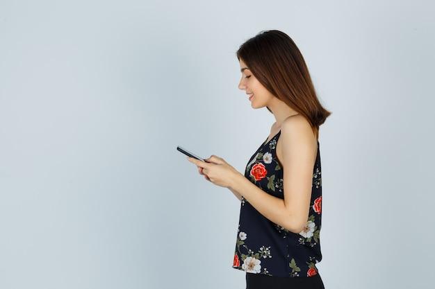 Portret van een jonge vrouw die naar een mobiele telefoon in een blouse kijkt en er vrolijk uitziet