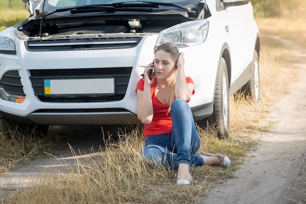 Portret van een jonge vrouw die naast een kapotte auto zit en om hulp roept