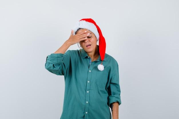 Portret van een jonge vrouw die ogen bedekt met de hand in shirt, kerstmuts en er uitgeput vooraanzicht uitziet