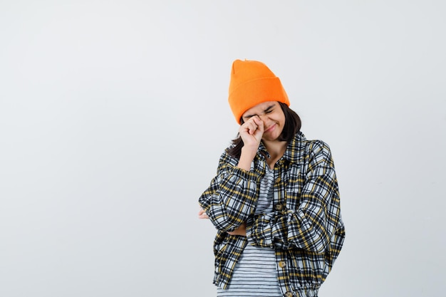 Portret van een jonge vrouw die ogen wrijft in oranje hoed en geruit hemd