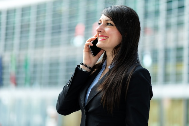 Portret van een jonge vrouw die op de telefoon spreekt